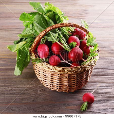 Fresh radishes in basket on wooden background