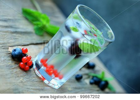 Glass of cold refreshing summer drink with berries and ice cubes on table close up