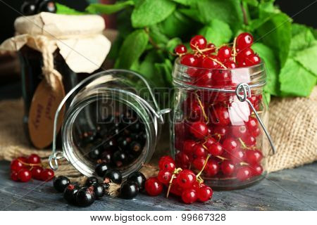 Ripe forest berries in glass jar  on wooden background
