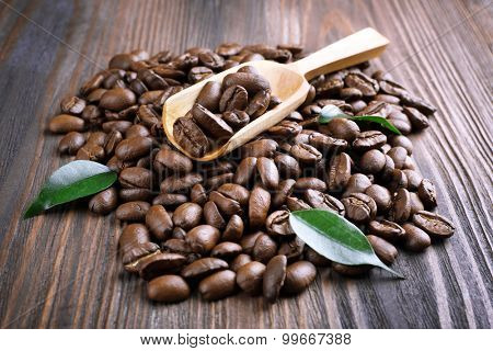 Coffee beans with leaves and spoon on wooden table close up