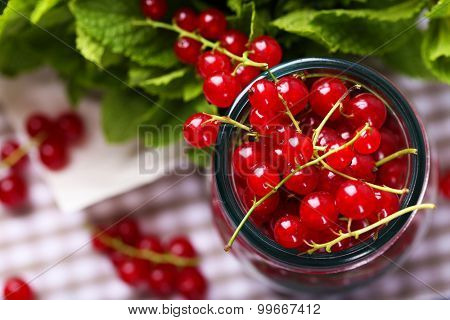 Fresh red currants in jar with mint on table close up