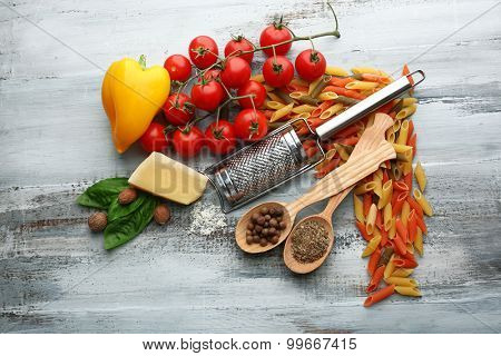 Pasta penne with tomatoes, cheese and basil on color wooden  background