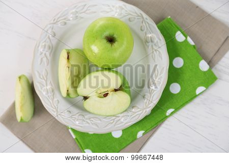 Green apples in plate on table with napkin, closeup