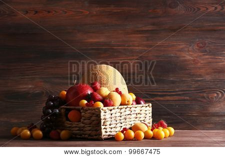 Assorted of fresh fruits in wicker basket on wooden background