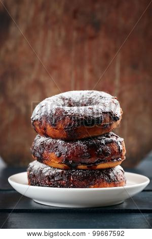 Delicious doughnut with chocolate icing on wooden background