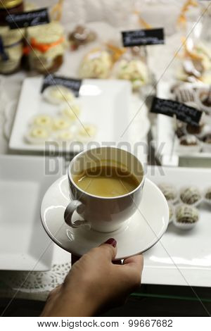 Female hand holding cup of coffee on table background
