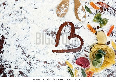 Row pasta with wooden spoons on flour background