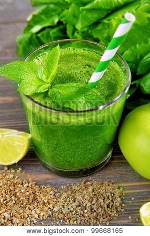 Green healthy juice with fruits and herbs on table close up