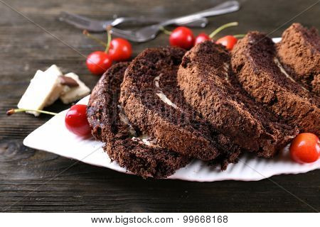 Delicious chocolate roll in white plate on wooden background