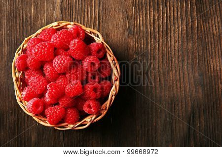 Fresh red raspberries on wooden table, top view