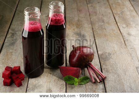 Glass bottles of beet juice on wooden table, closeup