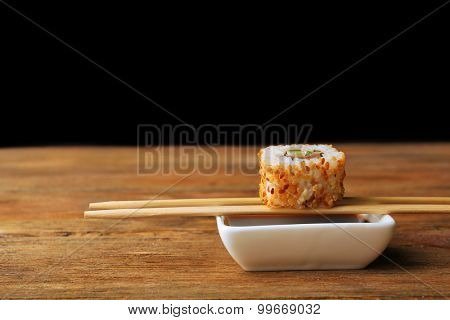 Roll with sauce and wooden sticks on dark background