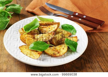 Baked potatoes with basil leaves in white plate on wooden table, closeup