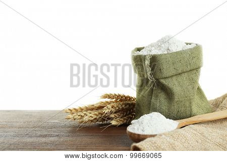 Wheat flour in burlap bag  on wooden table isolated on white