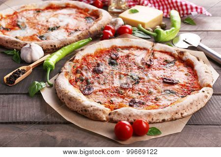 Delicious pizzas on wooden table, closeup