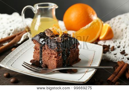 Portion of Cake with Chocolate Glaze and orange on plate, on table, on dark background