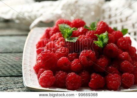 Sweet raspberries on plate on wooden  background