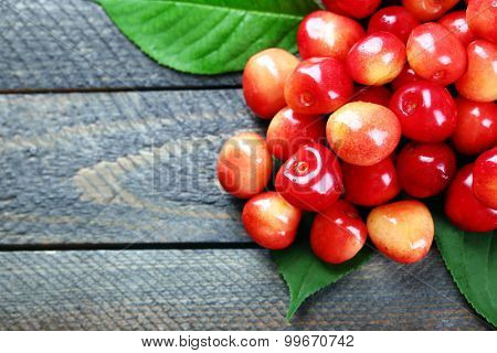 Sweet cherries with green leaves on wooden background