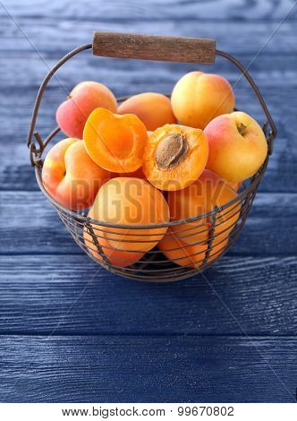 Ripe apricots on metal basket on wooden table close up
