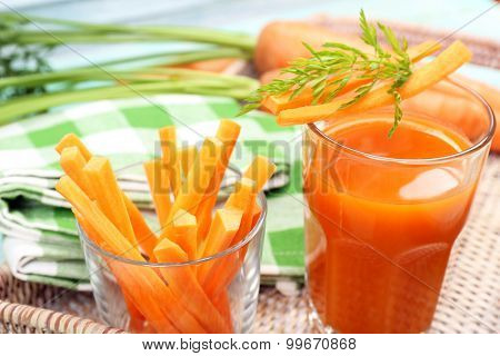 Glass of carrot juice with vegetable slices on table close up
