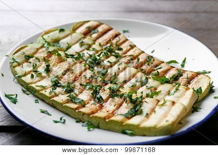 Grilled vegetable mallow in white plate on wooden table, closeup