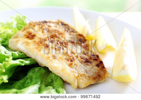 Dish of fish fillet with lettuce and lemon on plate close up