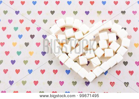 Sugar cubes in heart shape on paper background