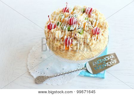 Butter cake with cherries on stand, on color wooden background