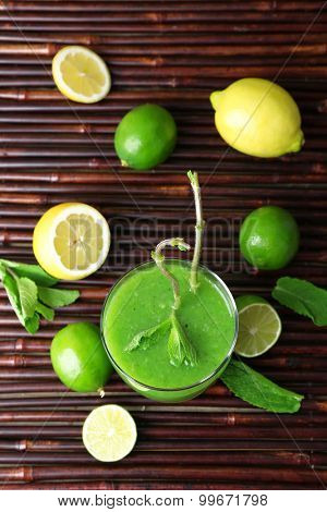 Glass of green healthy juice with mint and fruits on table close up