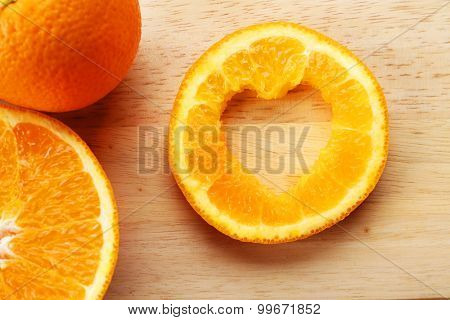 Orange slice with cut in shape of heart and fruits on wooden background