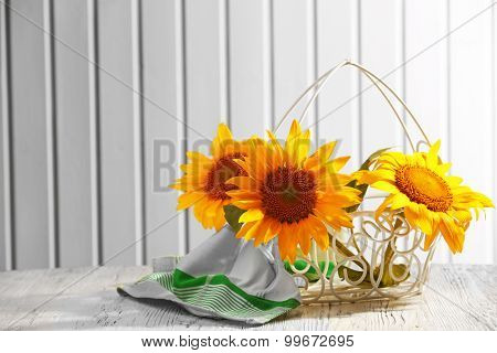 Beautiful bright sunflowers in basket on wooden background