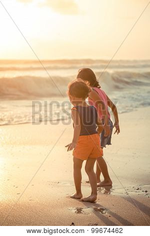 Two Little Girls Explore The Beach At Sunset