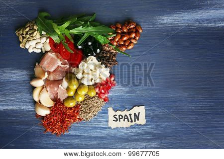 Map of Spain made with ingredients of traditional Spanish cuisine on color wooden background