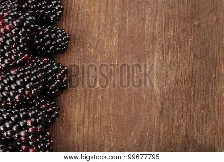 Ripe blackberries on wooden background