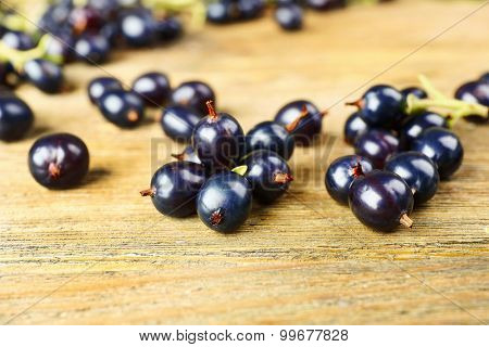 Ripe black currants on wooden background