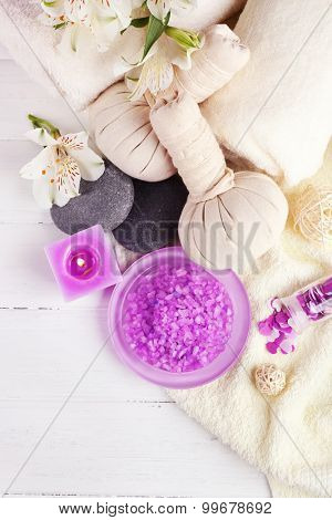 Massage bags with spa treatment and flowers on wooden table background