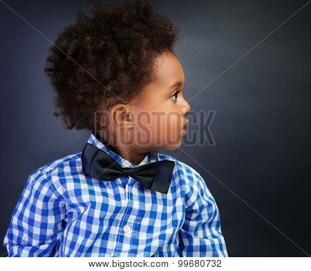 Portrait of cute little African schoolboy with surprise looking in side, over blackboard background, back to school