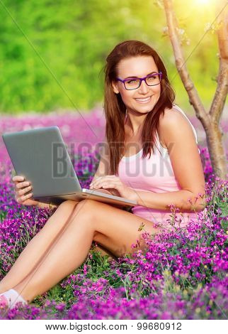 Happy student in university garden, cute cheerful girl doing homework outdoors on the notebook, education in high school, back to school