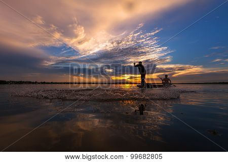 Silhouette throwing fishing net during sunrset Thailand