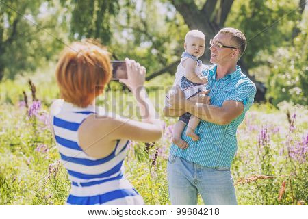 Family, Mother, Father And Baby In Nature Photographed On The Phone