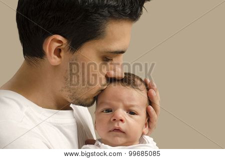 Loving Father Kissing His New Born Baby.