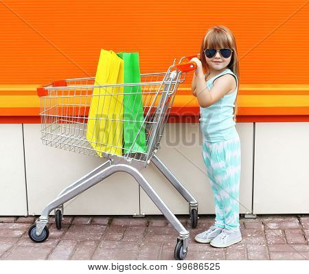 Little Girl Child And Shopping Cart With Bags Against The Colorful Orange Wall