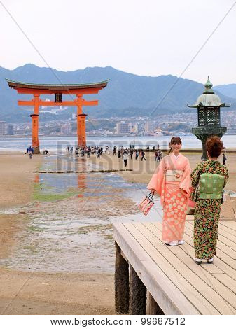 Japanese girls with red torii at Itsukushima island.