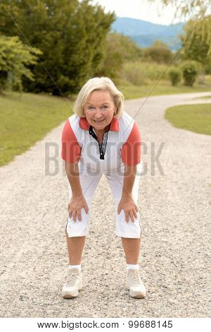 Athletic Elderly Woman Working Out On A Rural Road