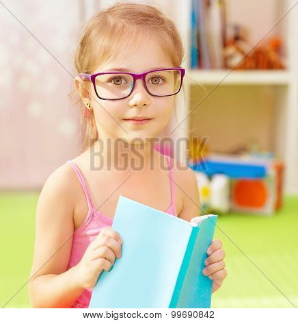 Portrait of cute little girl wearing glasses, spending time in daycare with book in hands and preparing to go to elementary school, start of education season