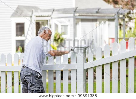 Active senior man painting a white picket fence