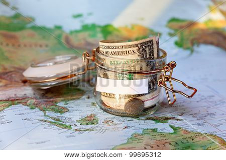 Collecting Money For Travel. Glass Tin As Moneybox With Cash Savings (banknotes And Coins) On Map.