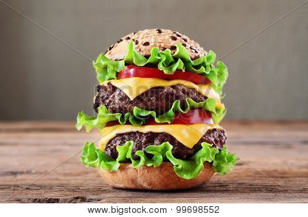 Hamburger closeup on a wooden table on a gray background