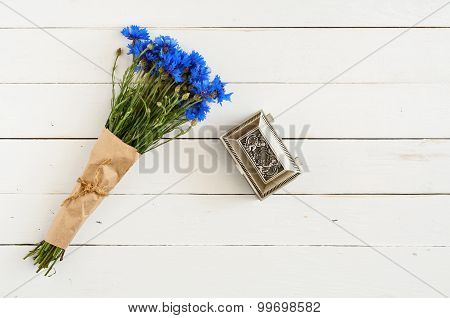 bouquet of flowers with old casket on a white wooden background