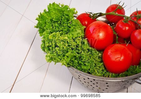 lettuce and tomato on a branch in a colander on a white wooden table closeup